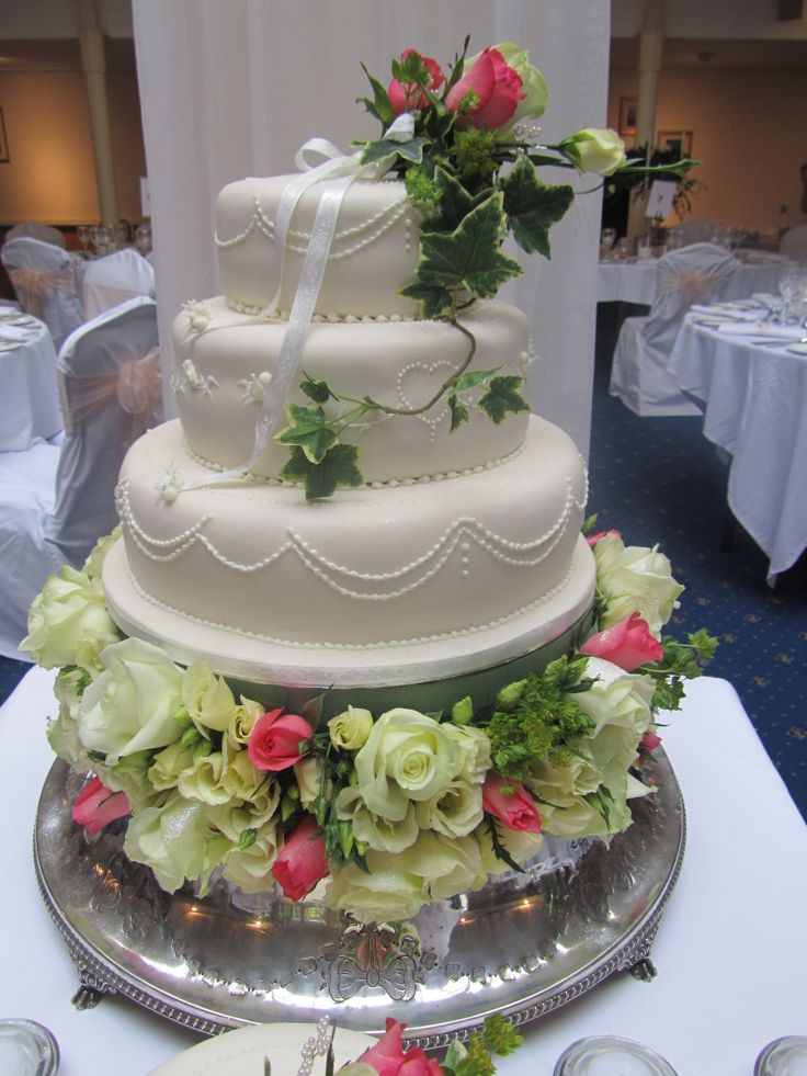 A beautiful cake base of coral and Ivory roses and Ivory Eustoma