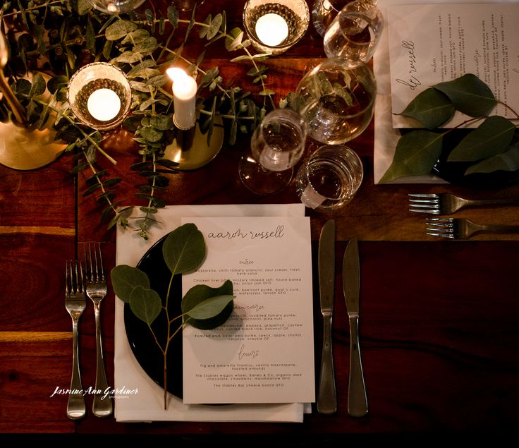 DY.o events (aka Duo) Candle lit table settings with eucalyptus and cursive font menus.