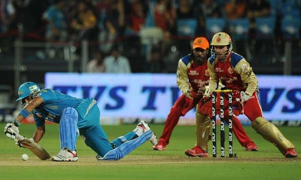 Royal Challengers Bangalore cricketers Chris Gayle (C) and AB De Villiers (R) watch as Pune Warriors India batsman Robin Uthappa (L) loses his footing while playing a shot during the IPL Twenty20  match between Pune Warriors India and Royal Challengers Bangalore at  Subroto Roy Sahara Stadium in Pune on May 11, 2012.