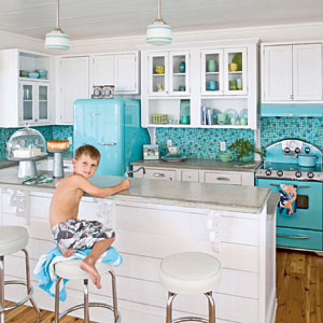 Retro kitchen elements mixed into modern designed home. Turquoise appliances white cabinets and blue tile backsplash
