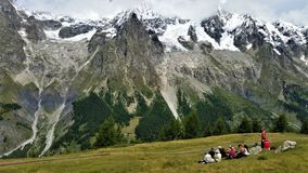 Hikers picnicking beneath snow-capped French Alps Royalty Free Stock Photo