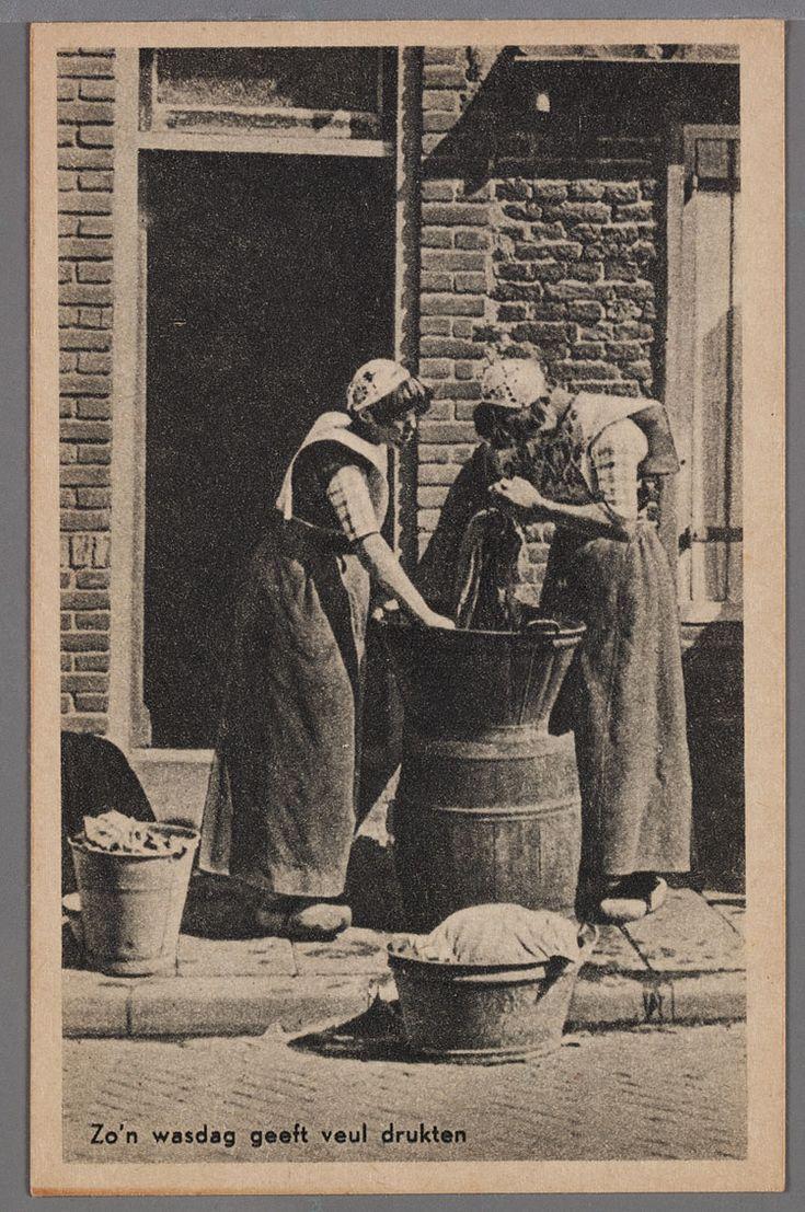 Twee vrouwen bij een zinken teil op een ton. Op de voorgrond een zinken teil en een emmer met wasgoed. De vrouwen dragen de gehaakte muts, een lichte kraplap, lichte geruite boormouwtjes en een effen werkschort. Klompen met een leertje. 1935-1955 #Utrecht #Spakenburg