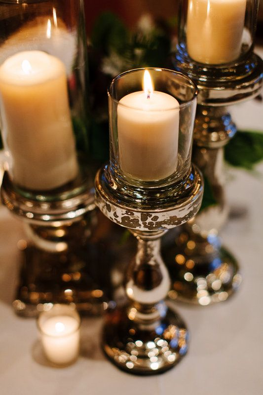wedding reception tables were set aglow with candles set on varying heights of mercury glass pillars, and votives.