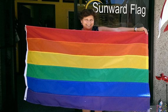 Our Rainbow flag is hand stitched and sewn in our flag shop in San Diego CA.  Using American materials and labor, we meticulously sew each stripe of the 6-colored flag and take great care in making sure your flag will boldly show your pride.  Our flags are finished with a canvas header and brass grommets.  Please view our Sunward Flag Etsy site for other PRIDE flags and sizes to choose from!  https://www.etsy.com/shop/SunwardFlag?ref=hdr_shop_menu  Ships to US and Ca...
