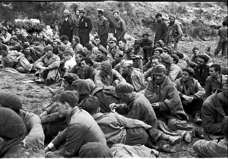 Spain - 1938. - GC - batalla del Ebro - Soldados republicanos sentados en el suelo preparados para escuchar un mitin.