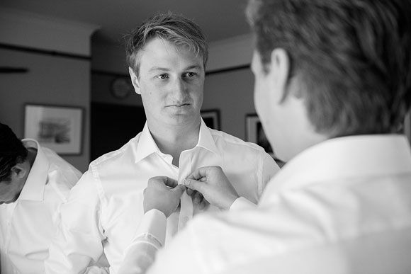 Normally we'd shoot the best man arranging the tie of the groom, but they didn't wear ties here, so buttoning a shirt sufficed.