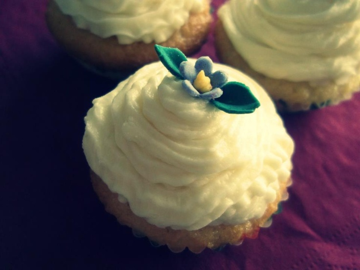 vanilla cupcake with vanilla buttercream topped with a flower made out of fondant
