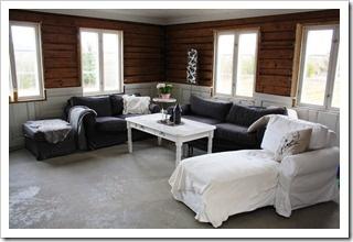 Livingroom with concrete floors, wooden walls and panel of old doors. Stue med betonggulv, tømmervegger og brystning av gamle dører.