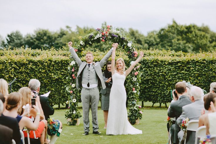 Bride & Groom raising their hands after they are married - Image by David Jenkins - Stephanie Allin Bride And Maids To Measure Bridesmaids For A Scottish Castle Wedding At Wedderburn Castle With Groom In Tartan Suit