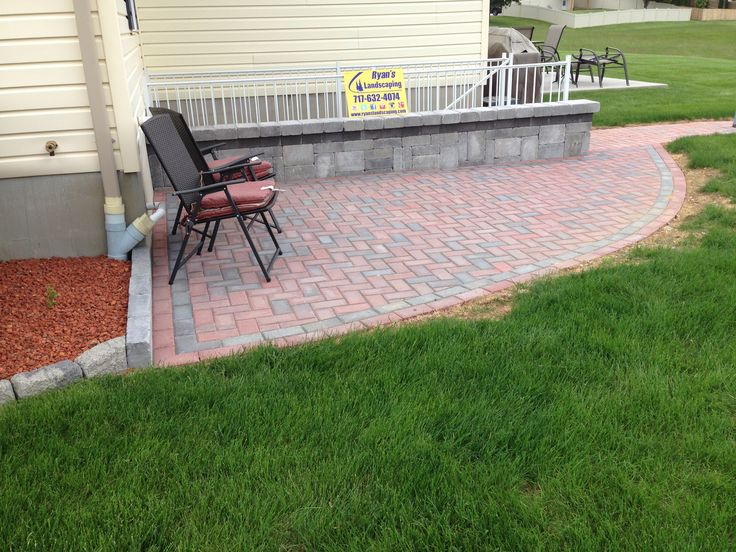 Hanover paver patio hardscape in 90 degree herringbone pattern featuring a seating wall with banding designed & constructed by Ryan's Landscaping in Hanover, Pa.