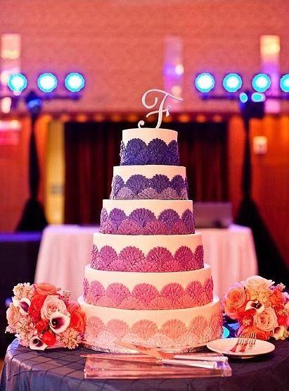 Sunset wedding theme. Sunset color theme. Sunset theme wedding cake on purple pintuck linen.
