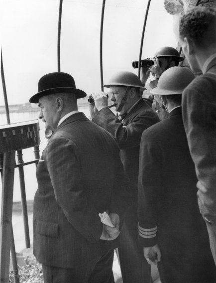 Wearing a steel helmet, English Prime Minister Winston Churchill is seen in an observation post in Dover, England, August 28, 1940, as he watched an air battle through field glasses. The mayor of Dover is shown at left.