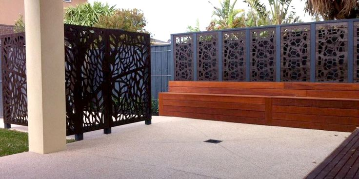 'Tree' and 'Pretoria' decorative screens line a concrete patio in a commercial development. These are QAQ designs.