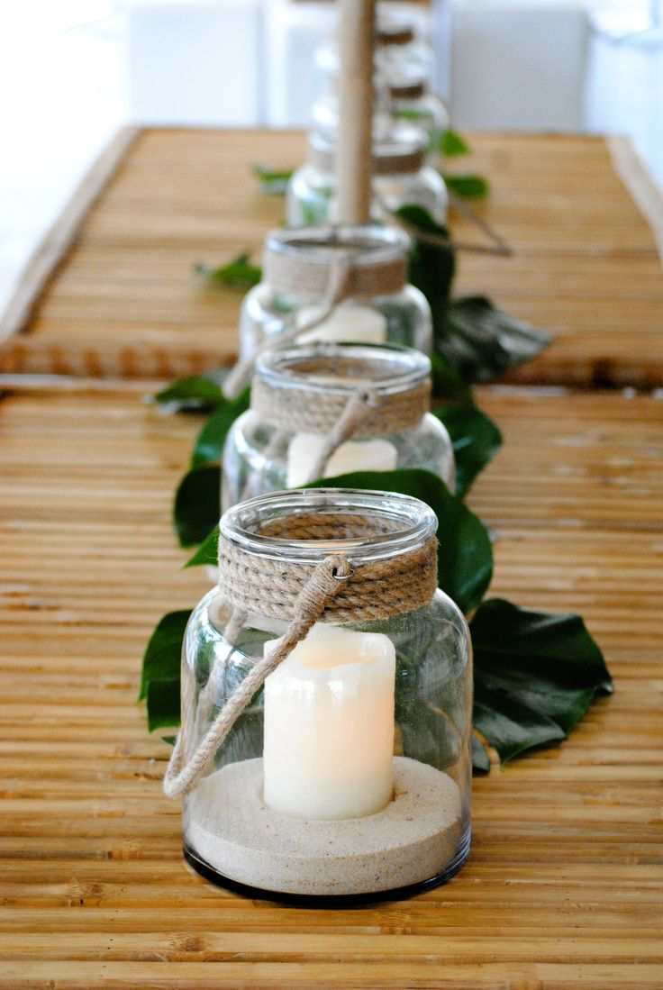 Tiki table styling with sand filled jars and candle light.