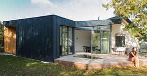 Extension contemporaine à Caluire et Cuire en ossature bois et bardage aluminium imitation zinc noir. Façade triangle, terrasse mélèze. L'extension s'ouvre sur une grande terrasse avec la vue d'un coté et le jardin de l'autre.