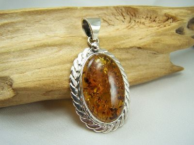 A beautiful and unique oval Baltic amber pendant in sterling silver mount.