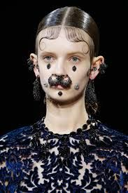 """Titled """"Victorian-chola girl"""", the Givenchy Fall Winter 2015 runway show was mesmerizingly arresting with its face jewelry, nude make up, curls and braid hair style. The faces embellished with gems and combined with large nose rings and ear pieces had a Goth-chic-vibe to it."""