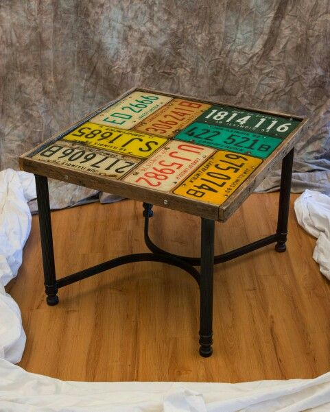 Vintage metal table, reclaimed pallet lumber border, repurposed license plate mounted on custom wood top. Top sealed with resin.