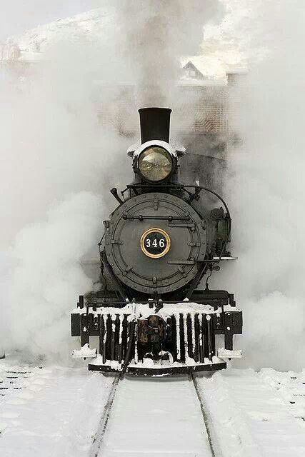Steam locomotive through steam and snow.