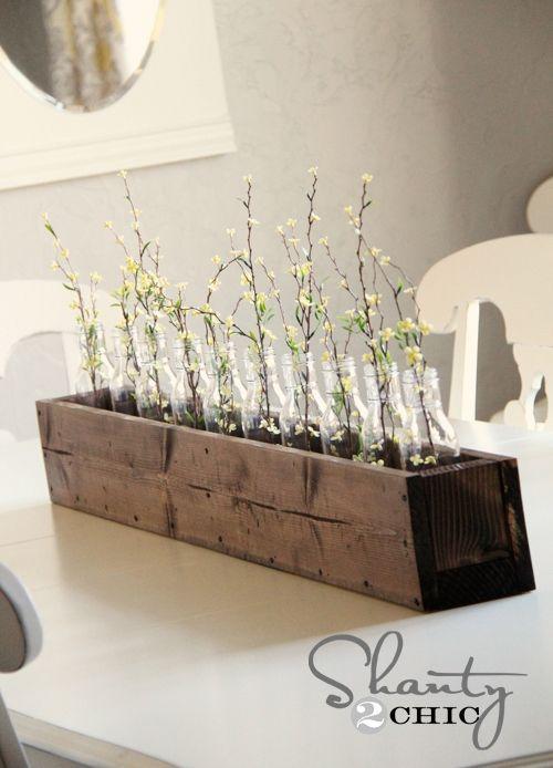 Un original centro de mesa hecho a base de un cajón de madera, unas botellas y unas flores.