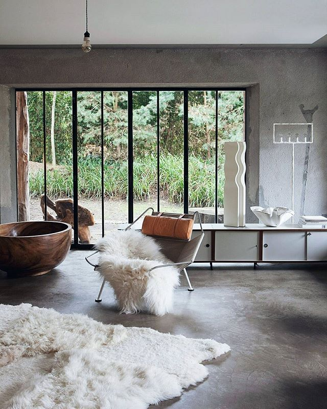 Make a modern home feel more warm and feminine with mixed materials and textiles, such as wood, concrete and faux fur