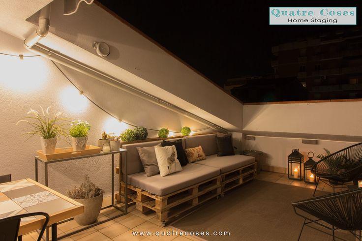 Terraza con sofa de pale, guirnalda luz, alfombra de exterior. fotografia noctura