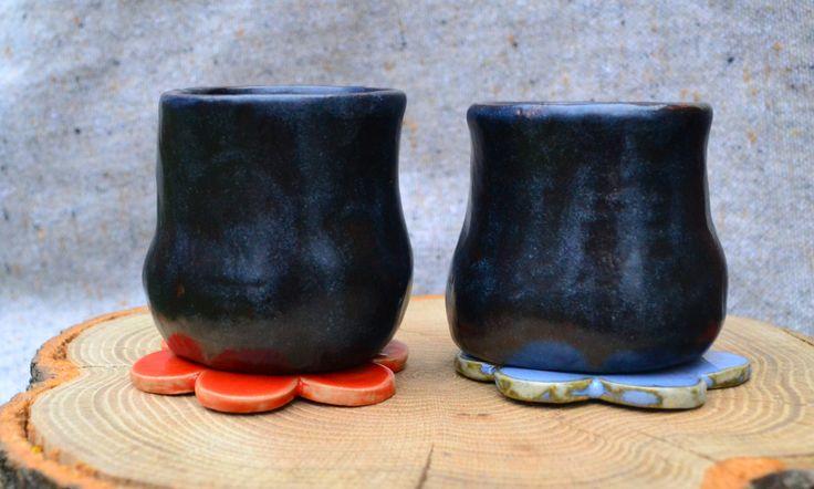 Ceramiczne czarki z podstawkami w kształcie kwiatów.