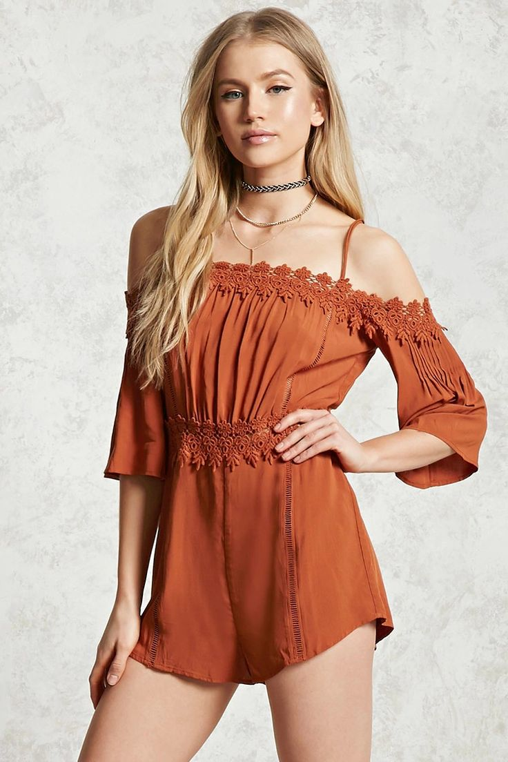 A woven romper featuring crochet trim and cutout waist detail, an open-shoulder design, ladder cutouts, dual cami straps, pintucked 3/4 sleeves, and a concealed back zip closure.
