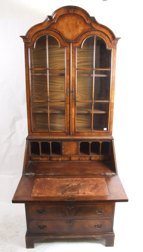 A slim walnut bureau bookcase in early 18th Century style. The shaped arched cornice above three adjustable shelves enclosed by astragal glazed doors. The fall flap enclosing a fitted interior above four long drawers on bracket feet. H. 206cm width 76cm