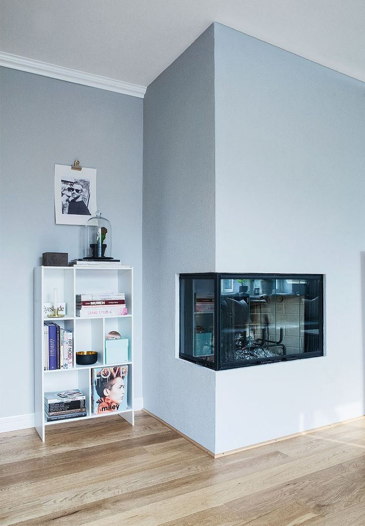 Built-in fireplace helps create coziness and warmth in the living room. Its dark look creates a good contrast to the baby-blue colour on the wall.