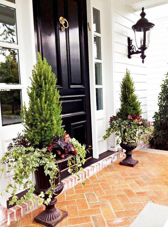 Black high-gloss front door with autumn urns.