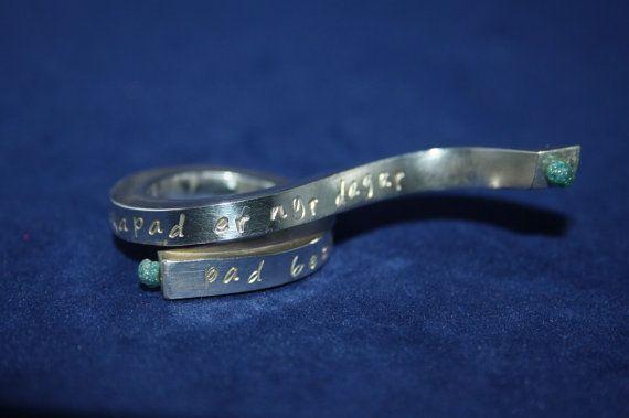 Dies ist mein persönlicher Ring (d.h. es ist ein Musterring).  Dieser Ring aus massivem 5 mm starken 935er Silber ist mit meinem Lieblingszitat punziert, in einer Welle auslaufend geschmiedet und mit wundervollen blauen Rohdiamanten versehen.  Dieser Ring ist mit anderen Edelsteinen und in anderen Materialstärken und -strukturen umsetzbar. Grundsätzlich sind die Werke der Design-Kollektion aber einzigartig und sollen Euch inspirieren. Preise der Schmuckstücke sind immer abhängig vom…