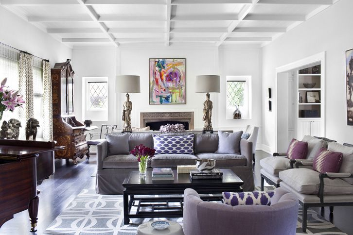 The gray upholstered furniture in the living room gets a bit of color with wonderful purple cushions.  Also love the statuette lamps on the console.