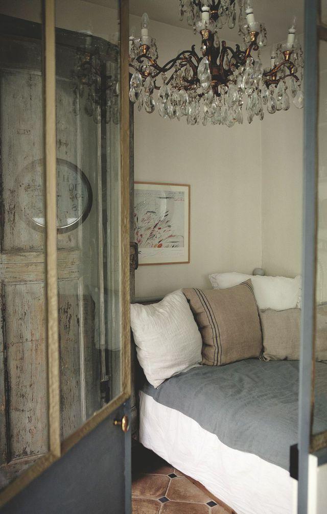 Dans la chambre des parents, portes de placards et lustre chinés en Italie.