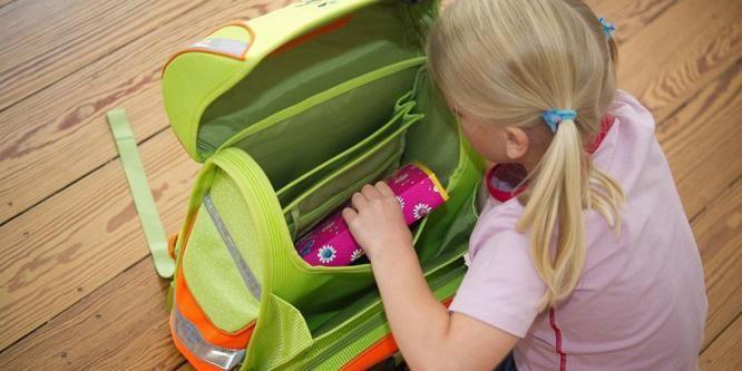 Bildet viser en jente som legger et pennal i en ryggsekk. Mandag er 6-åringene klare for sine første skoledag. Foreldre kan bruke tusener av kroner på nye klær, nye sko, ny sekk og en masse nytt utstyr. Tenk på miljøet, økonomien din og det sosiale. Ikke