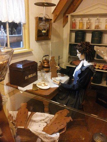 """In de foto zien we een welgestelde """"Joffer"""", zij is bezig met koekvergulden. Het maken van een 'vrijer'. Met Glazuur en bladgoud versierd ze de speculaas pop voor haar geliefde. (Foto gemaakt in het bakkerijmuseum Hattem)"""