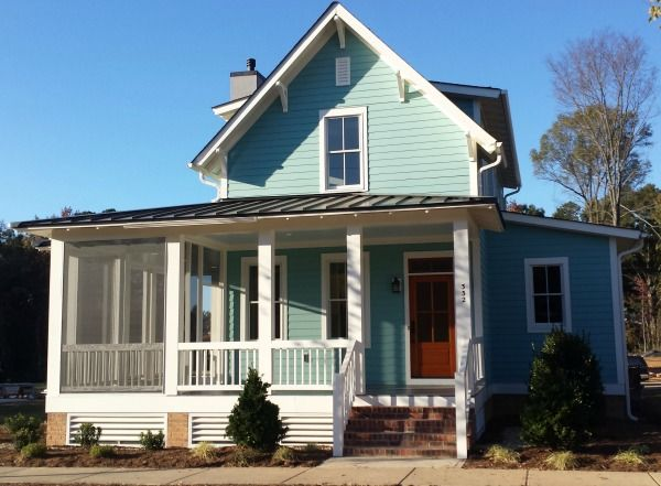 Sugarberry Cottage with aqua siding and an orange front door.
