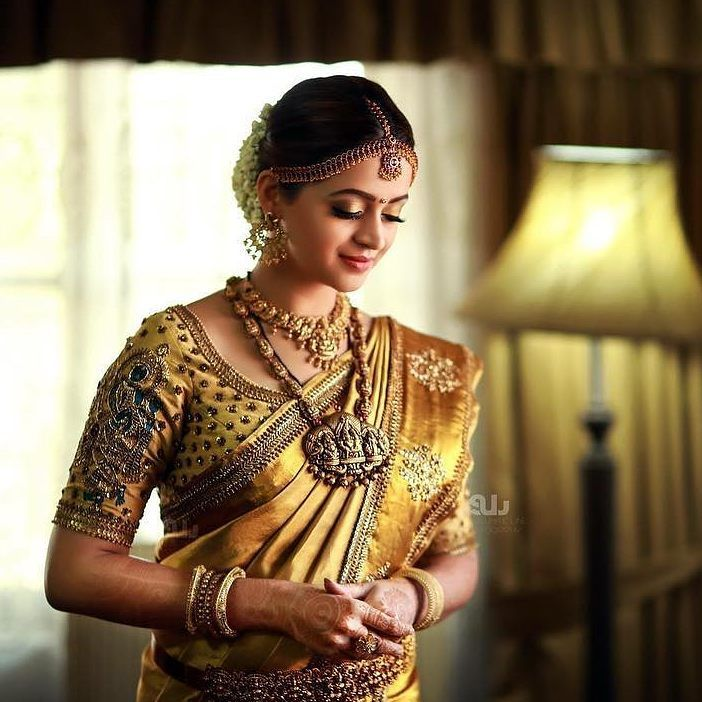 South Indian bride. Gold Indian bridal jewelry.Temple jewelry. Jhumkis. Red silk kanchipuram sari. Bun with fresh jasmine flowers. Tamil bride. Telugu bride. Kannada bride. Hindu bride. Malayalee bride.Kerala bride.South Indian wedding. Bhavana wedding. Pinterest: @deepa8