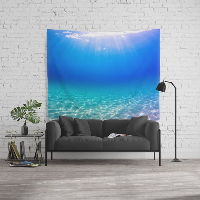 Underwater picture taken in Greece on a beautiful sandbeach with crystal clear water and the sun rays shining through the surface, creating a display of glowing patterns on the bottom. #underwater #water #sea #ocean #beach #summer #travel #adventure #blue #swimming #freediving #diving #homedecor #tapestry #wallart #walltapestry