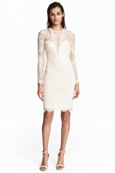 Knee-length lace dress with mesh sections at the top and on the sleeves, an opening with a button at the back of the neck and a seam at the waist. Half-line
