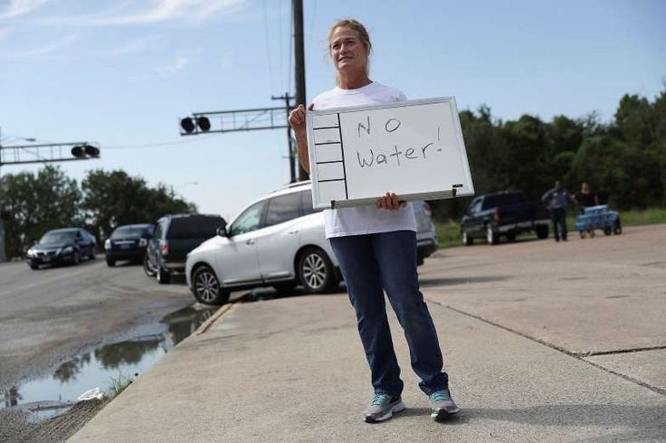 Barbara Nelson from Coastal Industrial and Specialty gas welding supplies store holds a sign that reads, 'no water', after they ran out of bottled water for people that are in need after the water supply to the city of Beaumont was shut down after Hurricane Harvey passed through on August 31, 2017 in Beaumont, Texas.