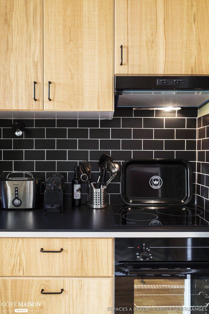 Une cuisine en bois moderne, avec crédence en carrelage mosaïque noir.