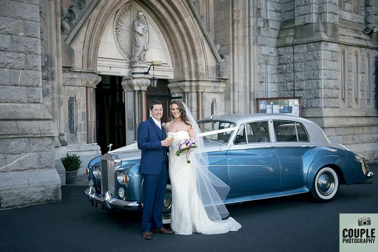 The bride & groom and their vintage blue wedding car outside the church. Weddings at The Knightsbrook Hotel Photographed by Couple Photography.