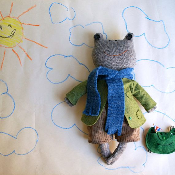 This sweet little toad comes with all the accoutrement a toad needs to get by in the world: green wool felt coat, striped brown linen shorts, blue wool scarf, stripey swim trunks, frog-head backpack, a little fish sandwich and a teeny paper boat. The toad is made from a recycled and washed secondhand suit coat in a classic tan tweed wool. He has brown button eyes and webbed hands and feet. He has a hand-embellished classic green coat made from wool felt--the coat has 3 hand-stitched pockets…