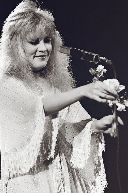Stevie, wearing a beautiful beaded and fringed shawl arranging roses on her microphone stand before performing a song from Fleetwood Mac's 'Mirage' Tour  ~  ☆♥❤♥☆  ~  http://bardotwitches.tumblr.com/post/120701238826