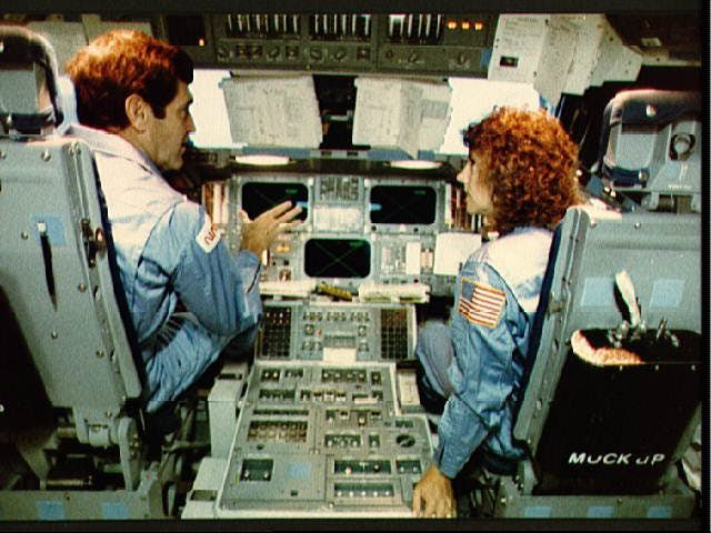 A picture of Dick Scobee and Christa McAuliffe sitting in the flight deck of the Challenger  space shuttle simulator.