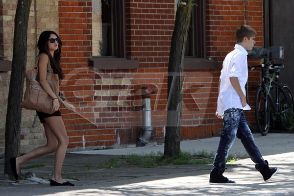 Selena and Justin sneaking out the back way to avoid the paparazzi. We really need to clean up the weeds
