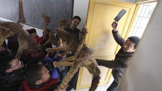 Studenti di una scuola elementare di Rugao, (provincia di Jiangsu) si esercitano durante una lezione di autodifesa con delle scope di saggina