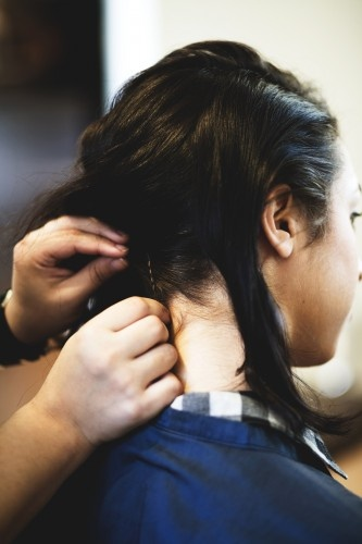 Sweep the curled hair to the side and pin at the nape of the neck. Then, release the side section above the ear.