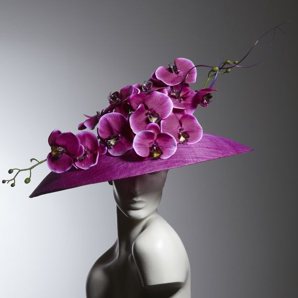 Philip Treacy i like the simple colour palette in this design. the Purple realistic flowers spread along the headpiece adds high to the flat dome base.
